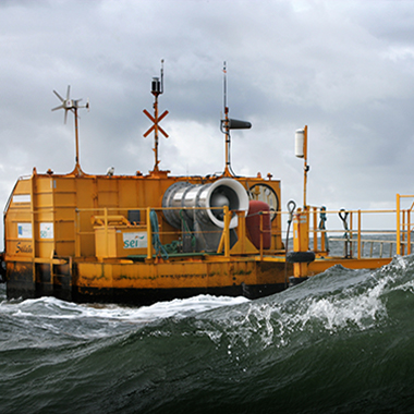 man with white hard hat standing in front of large wave energy platform